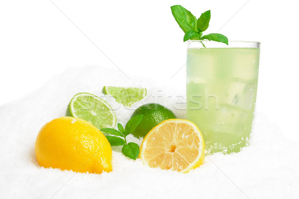 Glass of lime juice,lemons,ice cubes on snow on white Stock photo © dla4