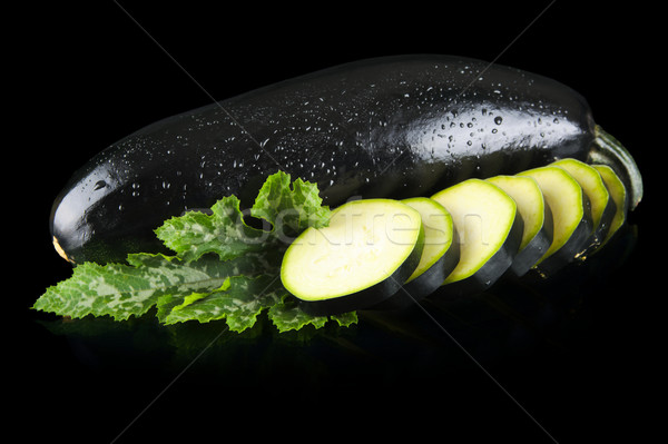 Wet courgettes cut into slices and leaves on black Stock photo © dla4