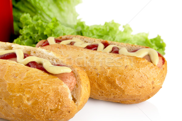 Hotdogs with ketchup with lettuce in the background on white Stock photo © dla4