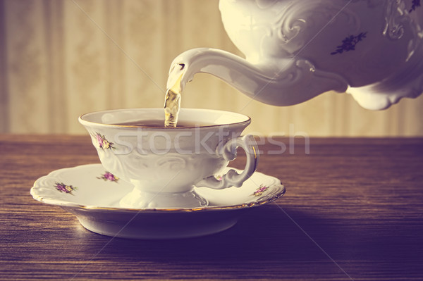 Old-fashioned pouring tea to cup on old wallpaper background Stock photo © dla4