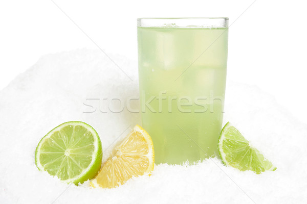Glass of lime juice with ice cubes,limes and lemons halves on snow on white Stock photo © dla4