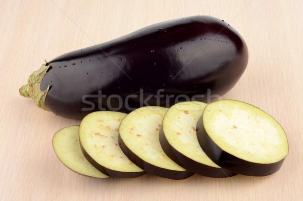 Studio shot single wet aubergine eggplant on wooden table Stock photo © dla4