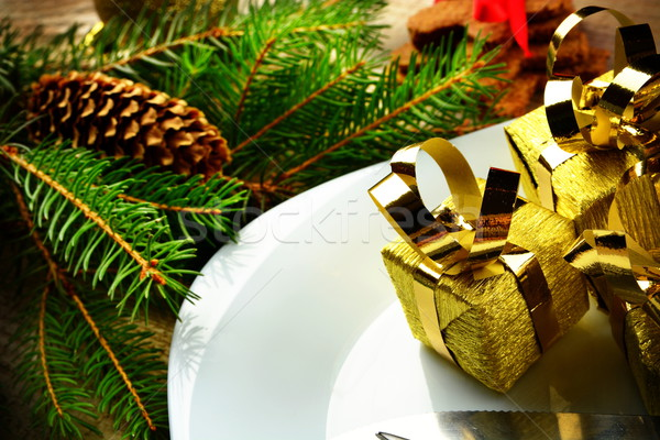 Closeup Christmas plate golden gifts pines wooden surface Stock photo © dla4