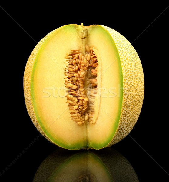 Melon galia notched with seeds isolated black in studio Stock photo © dla4