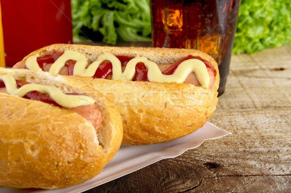 Hotdogs in the tray with ketchup with cola,lettuce on the wooden plank Stock photo © dla4