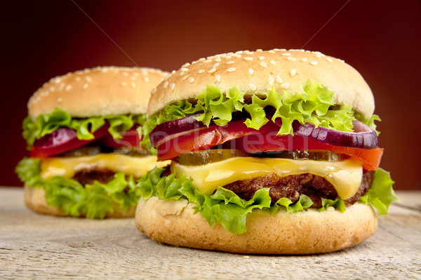Cheeseburgers on wooden table on burned background Stock photo © dla4