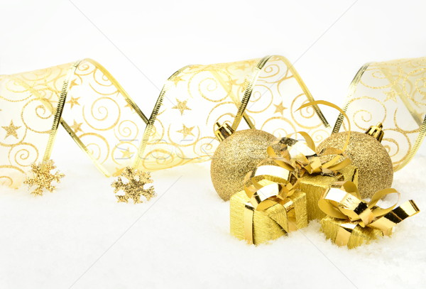 Golden christmas gifts,baubles with golden ribbon on snow Stock photo © dla4