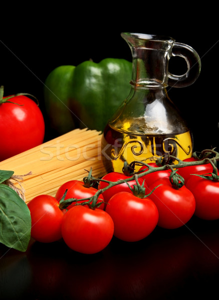Stock photo:  Long pasta raw isolated on black with tomatoes and olive oil