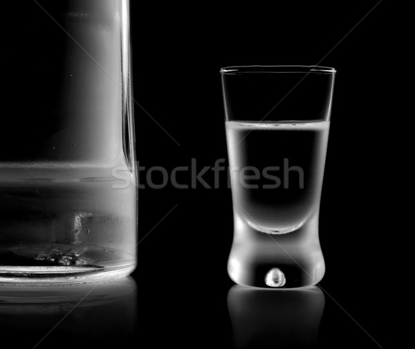 Bottle and glass of vodka standing isolated on black background Stock photo © dla4