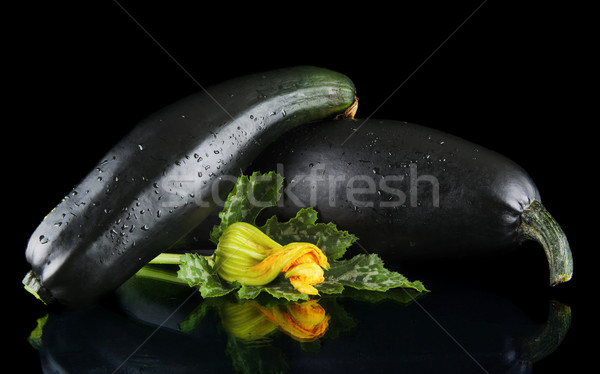 Wet mature courgettes with flowers on black background Stock photo © dla4