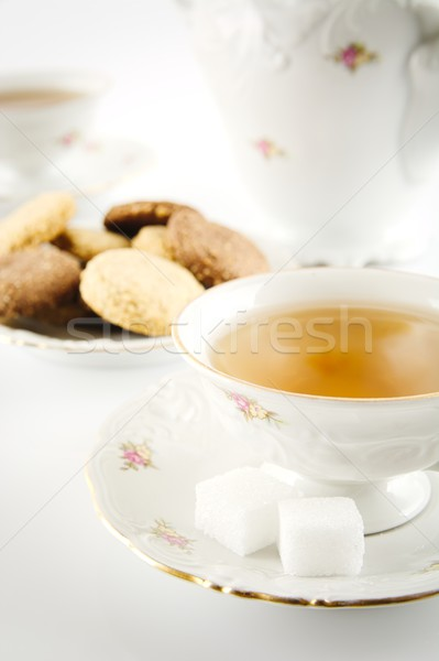 Old-style kettle with two cups of tea with cookies on white Stock photo © dla4
