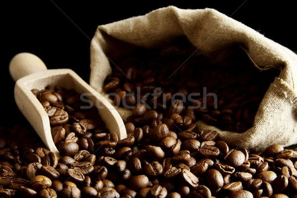 Overturned bag full of coffee beans on black with spatula Stock photo © dla4