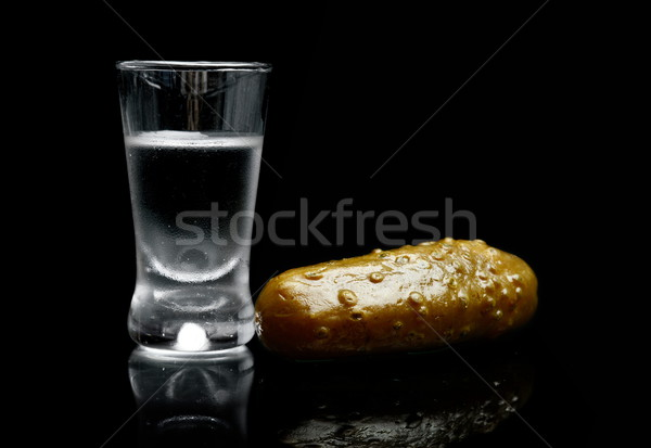 Glass of vodka with pickled cucumber isolated on black background Stock photo © dla4