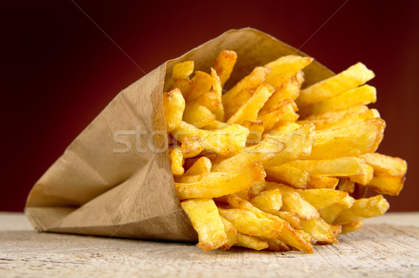 French fries in the paper bag on burned background on wooden table Stock photo © dla4