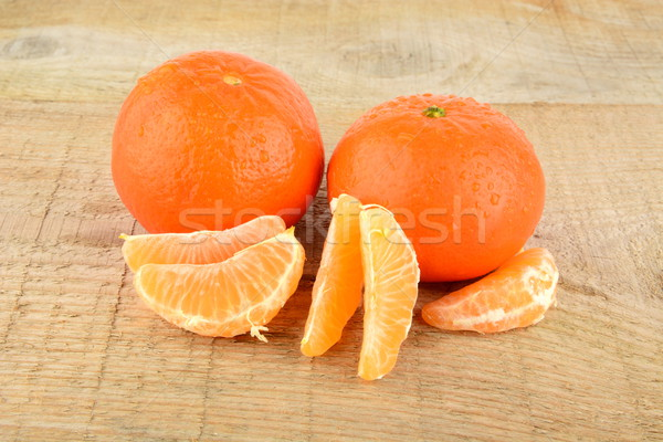 Mandarines with pieces isolated on wooden table Stock photo © dla4
