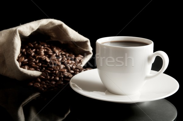 Cup of coffee with saucer with bag with coffee beans on black Stock photo © dla4