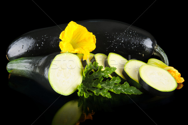 Wet courgettes cut into slices with flower and leaf on black Stock photo © dla4