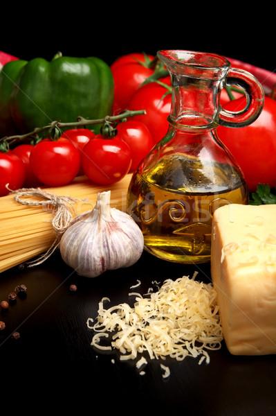 Pasta raw isolated on black with tomatoes,olive oil,garlic horiz Stock photo © dla4
