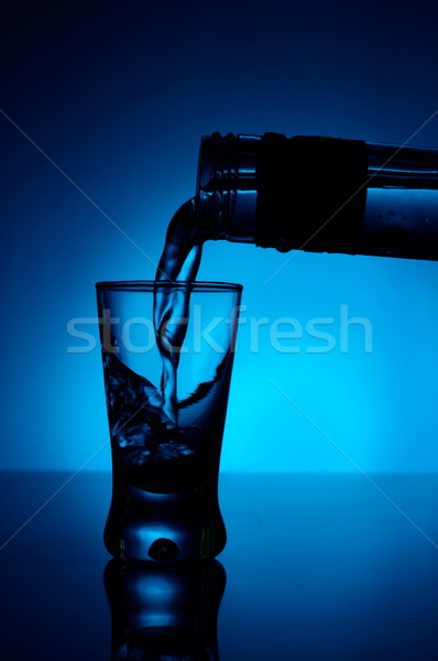 Vodka poured into a glass lit with blue backlight Stock photo © dla4