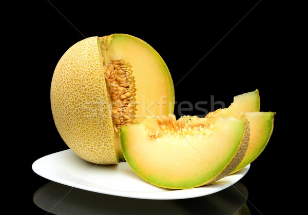 Melon galia with slices on plate isolated black in studio Stock photo © dla4