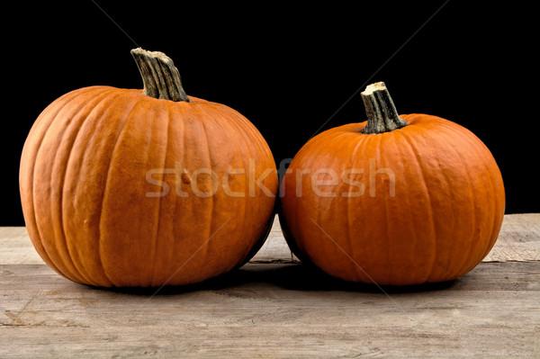 Closeup shot of beaded pumpkins on wooden board on black Stock photo © dla4