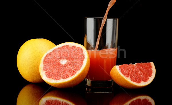 Studio shot sliced grapefruits with poured juice on black Stock photo © dla4