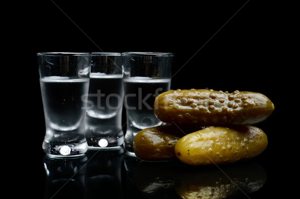 Many glasses of vodka with pickled cucumbers isolated on black background Stock photo © dla4