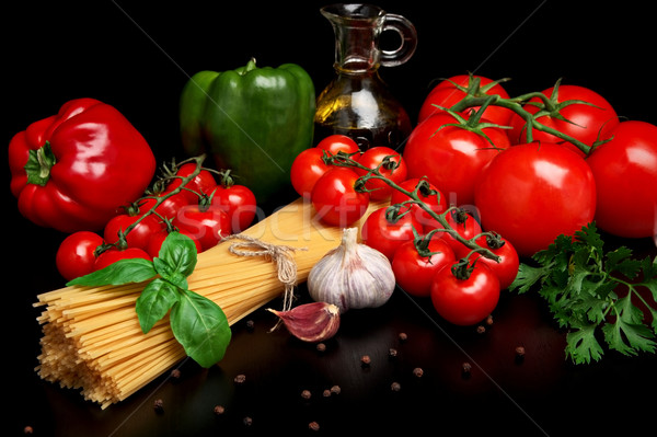 Pasta raw isolated on black with tomatoes,olive oil,garlic verti Stock photo © dla4