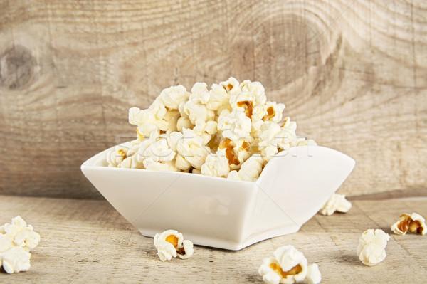 Bowl full of popcorn on wooden background Stock photo © dla4