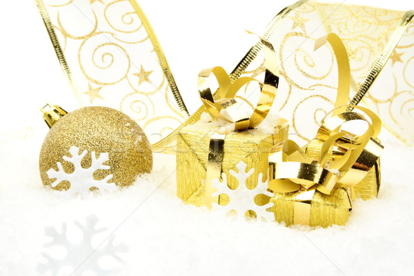 Golden christmas baubles, gifts,snowflakes with golden ribbon on snow Stock photo © dla4