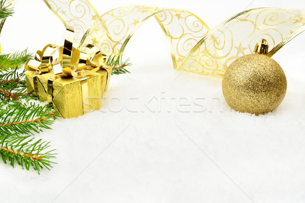 Golden christmas baubles with and needles fir and ribbon on snow Stock photo © dla4