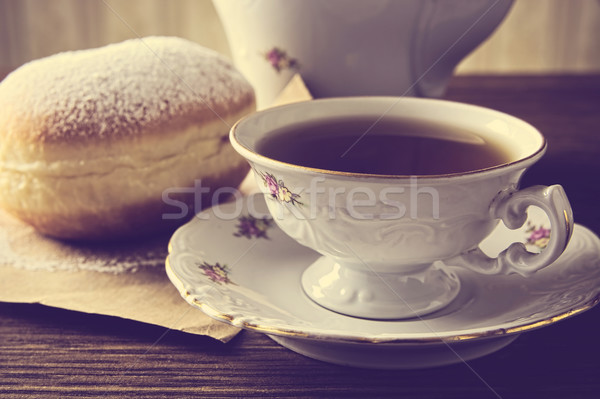 Closeup shot of donut with cup of tea on table in old-fashioned Stock photo © dla4