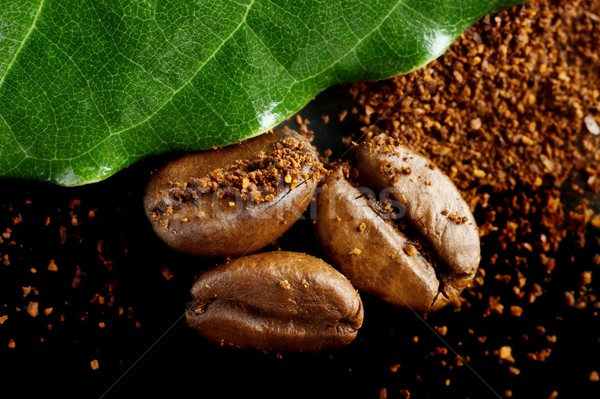 Closeup shot of coffee powder,beans with green leaf on black Stock photo © dla4