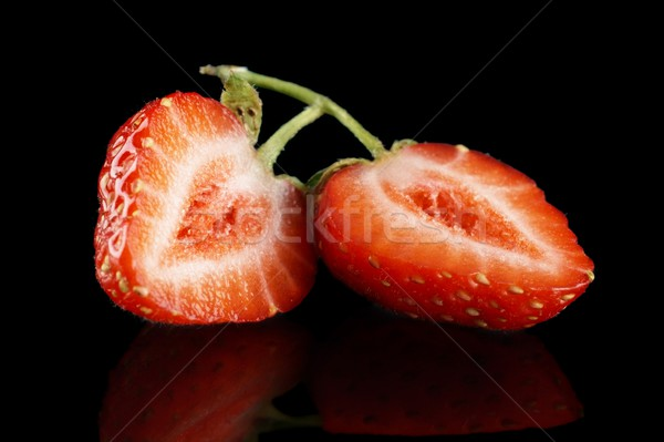 Halved strawberry isolated on black with green stalk Stock photo © dla4