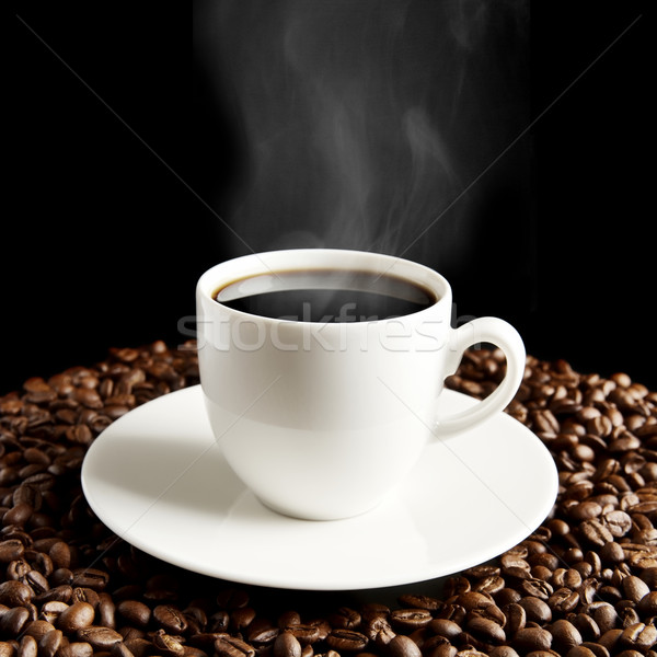 Cup of coffee with haze and coffee beans on black Stock photo © dla4