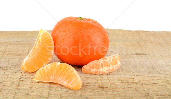 Mandarine with pieces isolated on wooden table Stock photo © dla4
