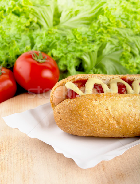 Hotdog with lettuce and tomatoes in the background on cutting bo Stock photo © dla4