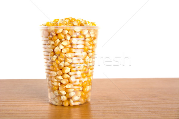 Plastic cup full of corn seeds on white Stock photo © dla4