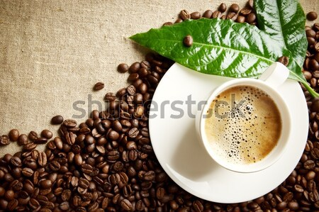 Macro cropped shot of frothy coffee with green leaf on linen cloth Stock photo © dla4