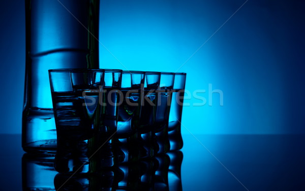 Bottle of vodka with many glasses lit with blue backlight Stock photo © dla4