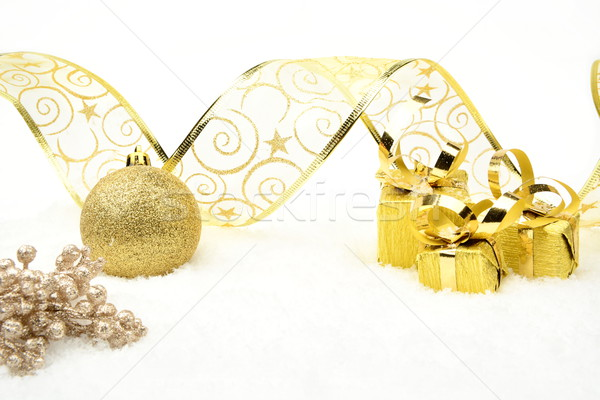 Golden christmas gifts,baubles ribbon and rowan on snow Stock photo © dla4