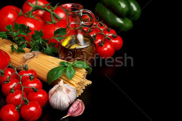 Pasta raw isolated on black with tomatoes,olive oil,garlic left  Stock photo © dla4