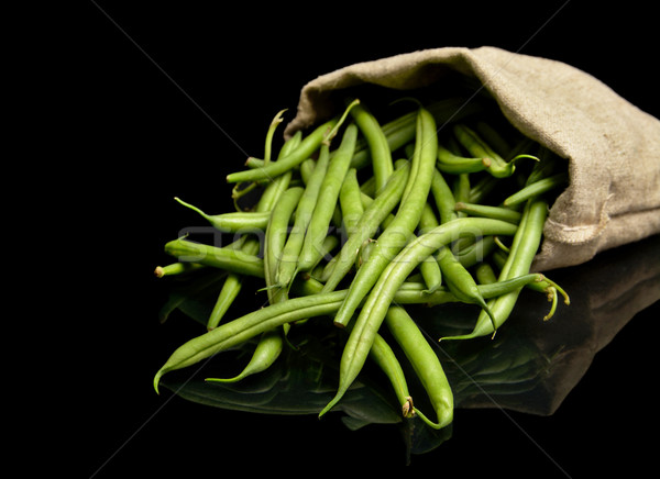 Stack of green beans in linen sack on black Stock photo © dla4