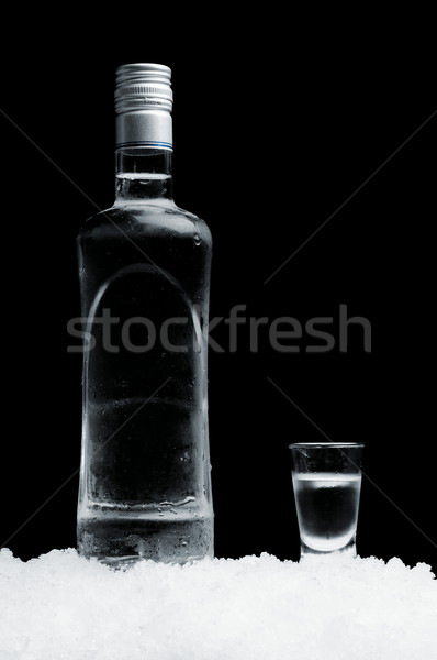 Bottle with glass of vodka standing on ice on black background Stock photo © dla4