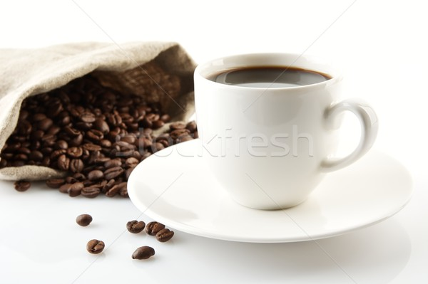 Cup of coffee with saucer with bag with coffee beans on white Stock photo © dla4