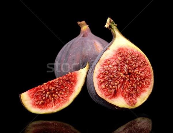 Three sliced figs isolated on black background Stock photo © dla4