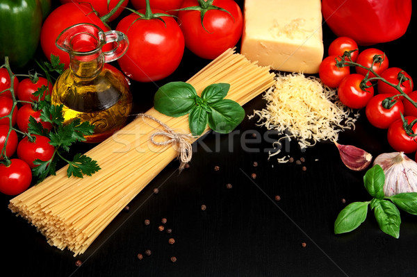 Pasta raw isolated on black with tomatoes,olive oil,garlic Stock photo © dla4