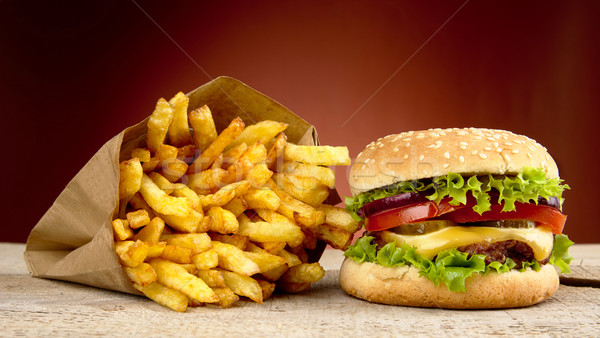 Cheeseburger, french fries on red background on wooden plank Stock photo © dla4