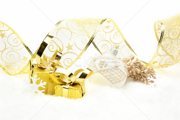 Golden christmas gifts, white bauble ribbon and rowan on snow Stock photo © dla4