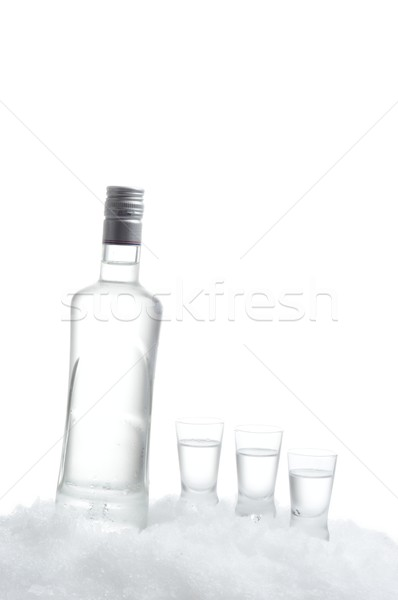 Bottle of vodka with glasses standing on ice on white background Stock photo © dla4